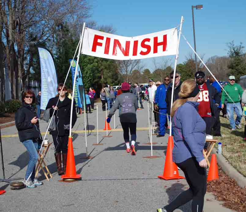 PTC Volunteers work the finish line at the New Years Day 5K